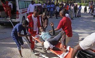 Des secouristes transportent un homme blessé dans un attentat à la voiture piégée, le 28 décembre 2019, à Mogadiscio, en Somalie.
