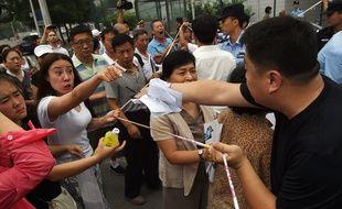 Des proches des passagers chinois du vol MH370 de la Malaysia Airlines font face à la police devant l'ambassade de Malaisie à Pékin, le 7 août 2015.