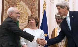 Le secrétaire d'Etat américain John Kerry (d) serre la main de son homologue iranien Mohammad Javad Zarif, le 9 novembre 2014 à Mascate, sous les yeux de Catherine Ashton (c) et du ministre omanais des Affaires étrangères Youssef ben Alaoui (2e d)