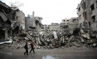 Des enfants passent devant des immeubles détruits dans la zone rebelle de Douma, à l'est de Damas, le 17 novembre 2015 en Syrie