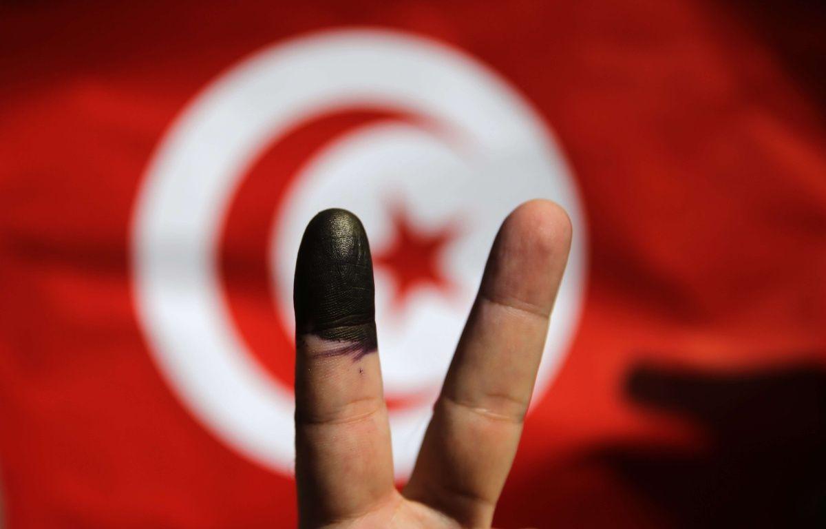 Un Tunisien qui vient de voter à l'ambassade de Tunisie au Caire montre son doigt marqué à l'encre devant un drapeau tunisien; le 25 octobre 2014. –  Hassan Ammar/AP/SIPA