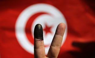 Un Tunisien qui vient de voter à l'ambassade de Tunisie au Caire montre son doigt marqué à l'encre devant un drapeau tunisien; le 25 octobre 2014.