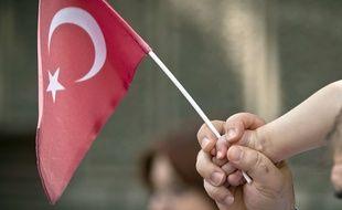 Illustration: un bébé tient un drapeau turc.