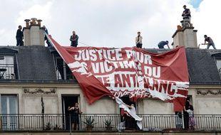 Des habitants d'un immeuble tentent de découper la banderole déployée par des militants d'extrême-droite, le samedi 13 juin 2020 à Paris.
