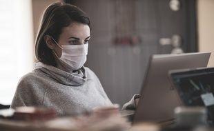 Une salariée qui travaille avec un masque.
