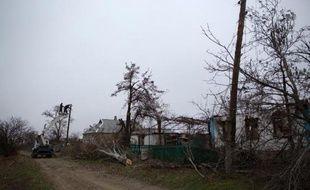 Réparation de lignes électriques endommagées par le combats, dans le village de Stepanivka, en Ukraine, le 19 novembre 2014
