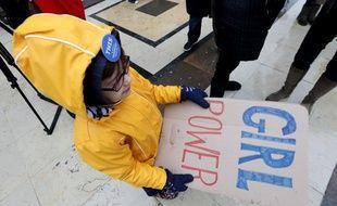 Une enfant tient une pancarte lors d'une manifestation contre les violences faites aux femmes à Paris.
