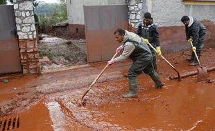Des habitants nettoient leur village hongrois, mardi 5 octobre 2010, après qu'une coulée de boue rouge a envahi les rues.