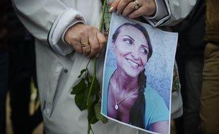 Dans une marche en hommage à Julie Douib à Vaires-sur-Marne, une femme tient un portrait de la jeune femme tuée par son ex-compagnon le 3 mars 2019.