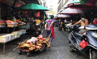 Une vendeuse ambulante pousse un chariot sur lequel ont été entassées des carcasses de chiens destinés à la consommation à Yullin, en Chine, le 20 juin 2018.