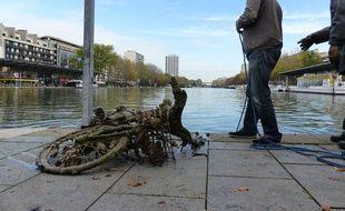 """Jeudi 5 novembre, des agents du service """"canaux"""" de la ville de Paris ramassent des déchets dans le canal de l'Ourcq pour l'artiste Michaël Pensky en vue de l'exposition «L'eau qui dort»."""