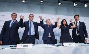 Les représentants des candidatures de Los Angeles et Paris pour l'organisation des JO 2024 et 2028, entourant le président du CIO Thomas Bach le 12 juillet 2017 à Lausanne.