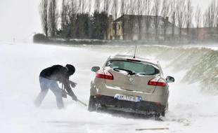Des personnes tentent de dégager leur voiture bloquée par la neige, le 12 mars 2013 près de Godewaersvelde dans le nord de la France