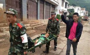 Rescuers carry an injuried child on a stretcher after a 6.1 magnitude earthquake hit the area in Ludian county in Zhaotong, southwest China's Yunnan province on August 3, 2014.  The quake struck 11 kilometres (seven miles) west-northwest of the town of Wenping at a relatively shallow depth of 10 kilometres at 4:30 pm (0830 GMT).      CHINA OUT   AFP PHOTO