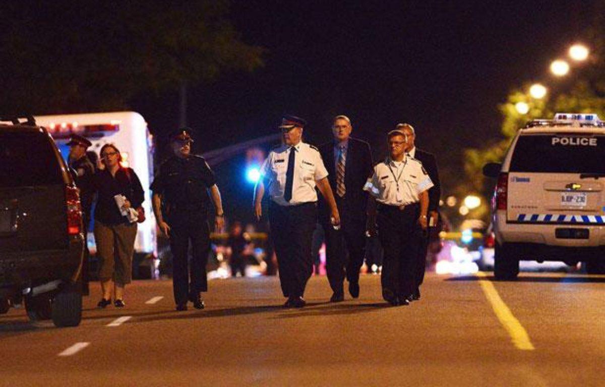 Le chef de la police de Toronto, Bill Blair (C), marche sur Morningside Avenue, près des lieux d ela fusillade qui a fait 2 morts et 19 blessés à Toronto, le 17 juillet 2012. – Aaron Vincent Elkaim/AP/SIPA