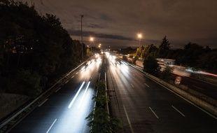 Une autoroute la nuit avec de la circulation automobile. (Illustration)