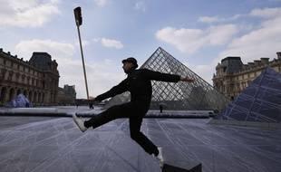 JR devant la pyramide du Louvre lors de l'installation géante de son oeuvre en mars 2019