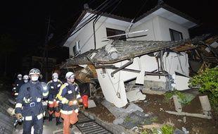 Des pompiers près d'une maison effondrée à Mashiki, dans le département de Kumamoto, après le tremblement de terre qui a secouée le sud-ouest du Japon dans la nuit du 14 au 15 avril 2016.
