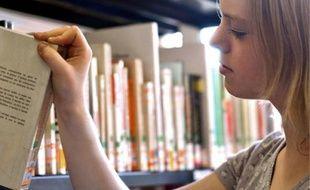 Une jeune femme choisit un livre dans une bibliothèque