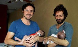 Un couple d'homosexuels espagnols José Antonio Fernandez (g) et Luis Delgado posent avec leurs bébés à Cancun au Mexique, le 18 février 2015
