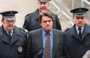 Photo d'illustration du 26 mars 1996 montrant Bernard Tapie entouré de deux policiers arrivant au palais de justice de Béthune.