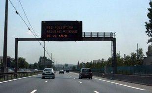 Des voitures circulent à Lyon sous un panneau demandant aux automobilistes de réduire leur vitesse