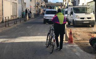 Un cycliste descendu de son vélo, près de la place Salengro, sur le faubourg Figuerolles