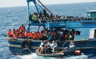 Illustration - Un bateau de migrants en train d'être secourus dans la mer Méditerranée.