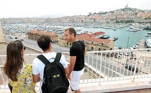 Max, Marseillais bénévole, fait découvrir avec enthousiasme sa ville à un couple de Brésiliens.