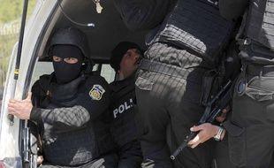 Des policiers tunisienscagoulé dans un véhicule, le 18 mars 2015