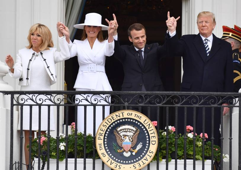 US President Donald Trump (R), French President Emmanuel Macron (2nd R), US first Lady Melania Trump (2nd L) and Brigitte Macron (L) salute the crowd from a balcony during a welcome ceremony at the White House in Washington, DC, on April 24, 2018.