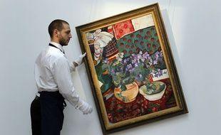 Un employé de Sotheby's accroche un tableau de Nathalie Gontcharoff à Londres, en 2012.