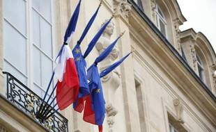 Des drapeaux français et européens liés par un ruban noir en hommage aux victimes du crash d'un avion d'Air Algérie, le 28 juillet 2014 à l'Elysée, à Paris