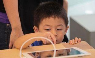 Un enfant joue avec un iPad dans un Apple Store (illustration).