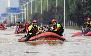 Des sauveteurs du service d'incendie et de secours de la ville de Yangzhou, dans l'est de la Chine, évacuent des personnes d'un hôpital à la suite de fortes pluies à Zhengzhou, dans la province chinoise du Henan, le 22 juillet dernier.