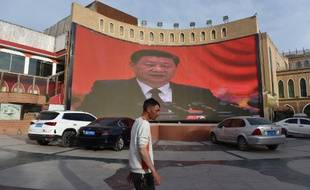 Cette photo prise le 4 juin 2019 montre un homme passant devant un écran montrant des images du président chinois Xi Jinping à Kashgar, dans la région du Xinjiang, au nord-ouest de la Chine.