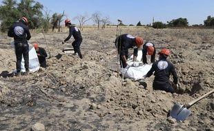 Des casques blancs syriens déterrent des restes humains d'une fosse commune près de Raqa, en Syrie.