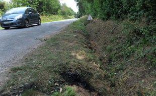 Une voiture passe sur le lieu d'un accident qui a coûté la vie à quatre mineurs à Rohan, dans l'ouest de la France, dans la nuit du 1er au 2 août 2015