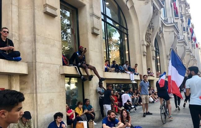 Des fans assis sur les façades d'enseignes longeant l'avenue des Champs-Elysées.