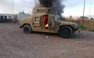 Photo prise d'un véhicule blindé de l'armée irakienne en feu, le 10 juin 2014 à Mossoul, deuxième ville du pays, contrôlée désormais par les jihadistes