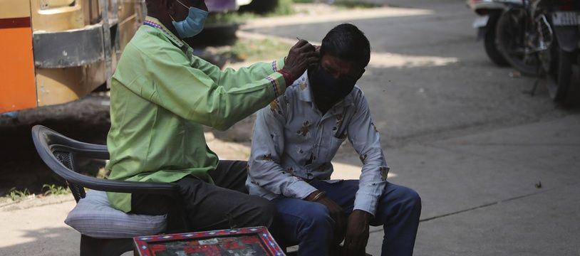 Un homme nettoyant l'oreille d'un autre en Inde, le 11 septembre 2020.