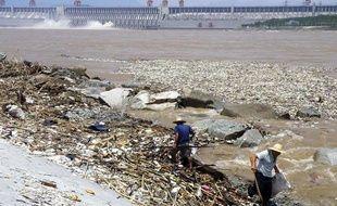 Des ouvriers chinois ramassent les ordures du fleuve Yangtse face au barrage des Trois Gorges.