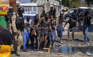 La police conduit un groupe de détenus qui se sont évadés de la prison de la Croix-des-Bouquets avant de se faire rattrapés, jeudi 25 février.