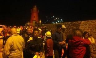 """Passagers évacués du """"Costa Concordia"""" arrivant sur l'ile de Giglio la nuit du 13 au 14 janvier 2012 ; les lumières du navire sont visibles en arrière plan."""