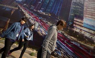 Pékin, le 19 octobre 2015. Illustration de Chinois devant une affiche.