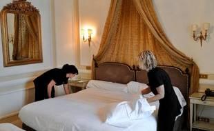 Deux femmes de chambre refont un lit dans un hôtel (Photo d'illustration)