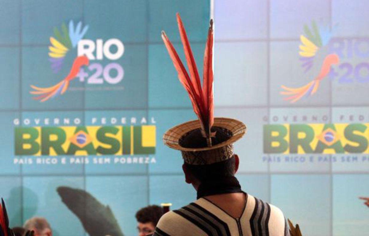 Un Indien d'Amazonie devant une affiche du sommet sur l'environnement Rio+20, à Brasilia en juin 2012. – Eraldo Peres/AP/SIPA