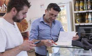 Samer (en bleu) et Guillaume font les courses ensemble pour préparer un menu inspiré de la cuisine syrienne, qui sera présenté lors du Refugee Food Festival de Lyon.