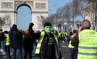 Un «gilet jaune» masqué défile sur l'avenue des Champs-Elysées, le 2 mars 2019.