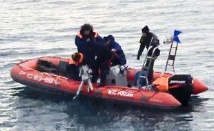 Des employés du ministère russe des situations d'urgence cherchant des morceaux d'avion après le crash en mer noire, le 26 décembre 2016